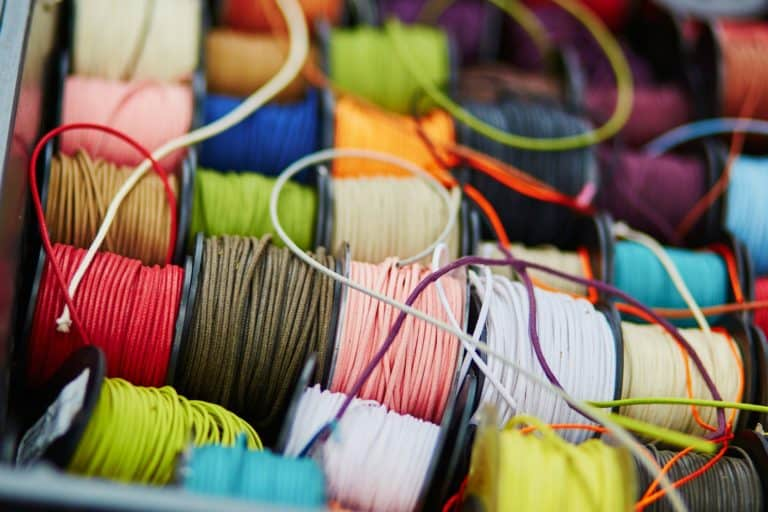 Variety of spools with rope of different colors for sewing or crafting on a market